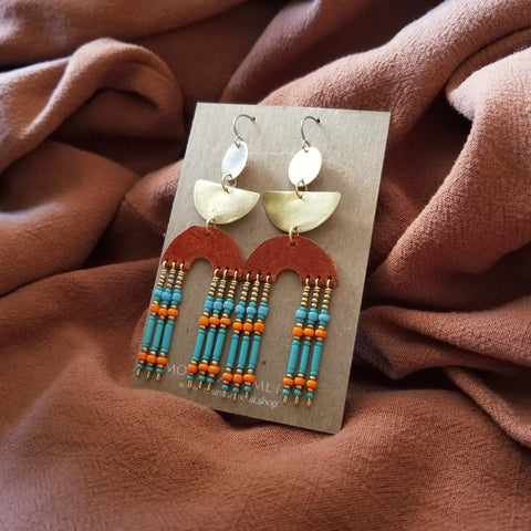 Earrings made with upcycled leather, seed beads, brass geometric shapes and hypoallergenic titanium ear wires. Orange colored leather in rainbow shape with beaded fringe. Turquoise, orange, and gold colored seed beads.