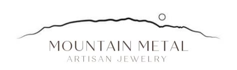 Mountain Metal Artisan Jewelry Logo. Outline of the Sandia Mountains of New Mexico with a rising moon.