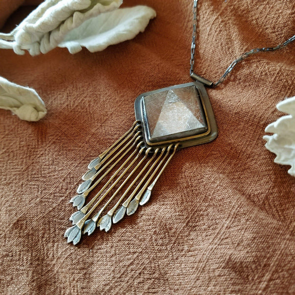 Handmade one of a kind necklace with rutilated quartz set in sterling silver and brass with eleven hand engraved snowdrop flower fringe dangles. All hanging on a sterling silver chain.