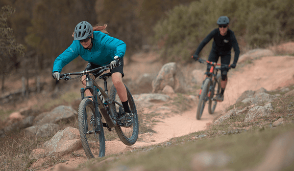 Two cyclists taking on an aggressive dirt trail on their mountain bikes