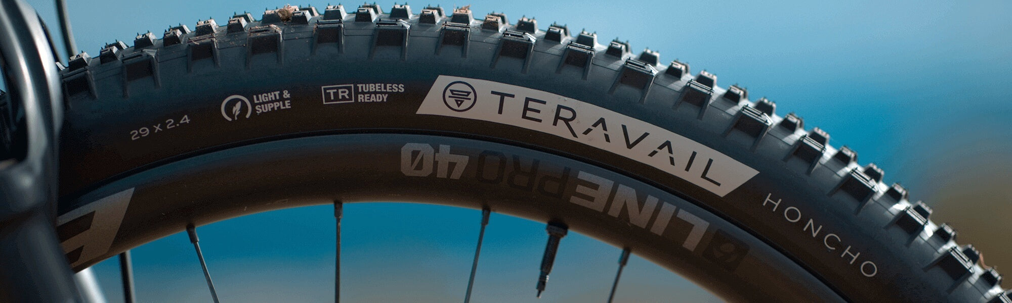 Closeup of Teravail Honcho tire mounted on a wheel, with focus on sidewall and hotpatch