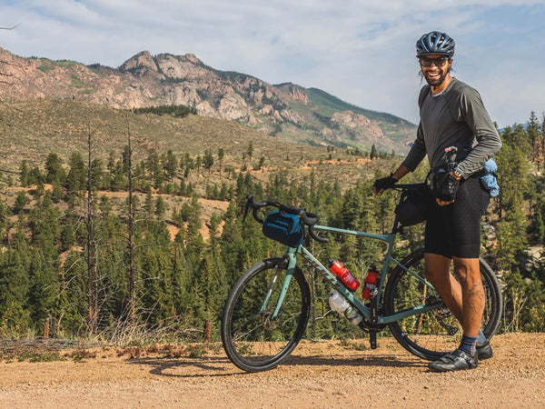 Jalen Bazile standing with his gravel bike in front of tree-lined mountain range