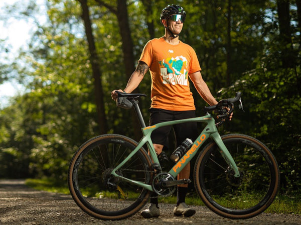 Jamie Bestwick standing with his gravel bike on a tree-lined trail