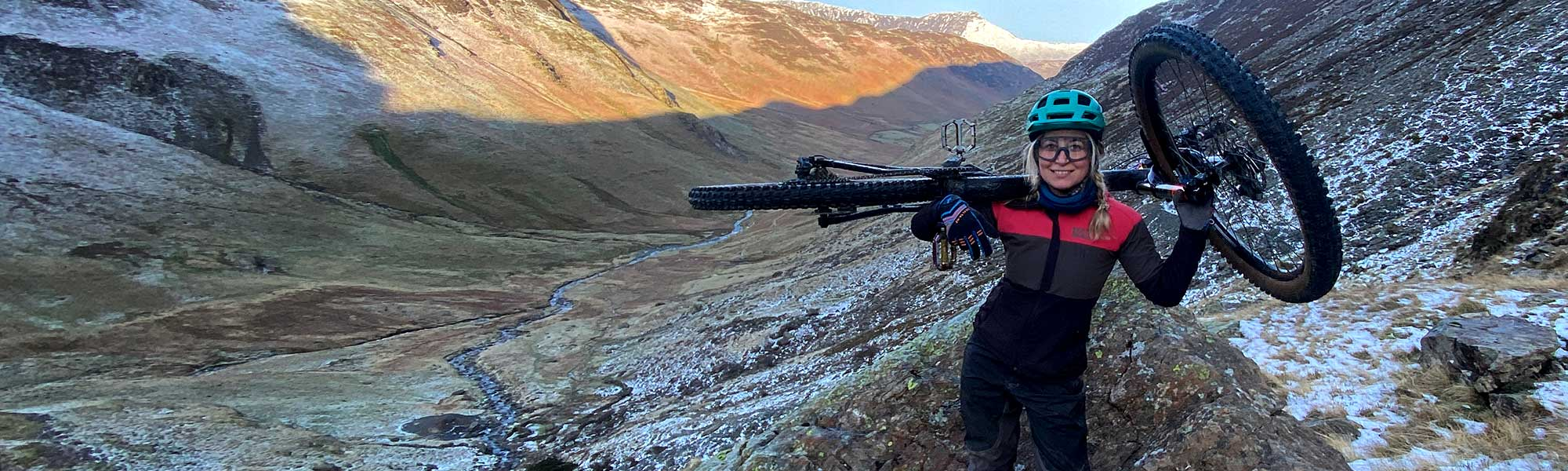 Kate O'Callaghan holding her bike across her shoulders in the mountains