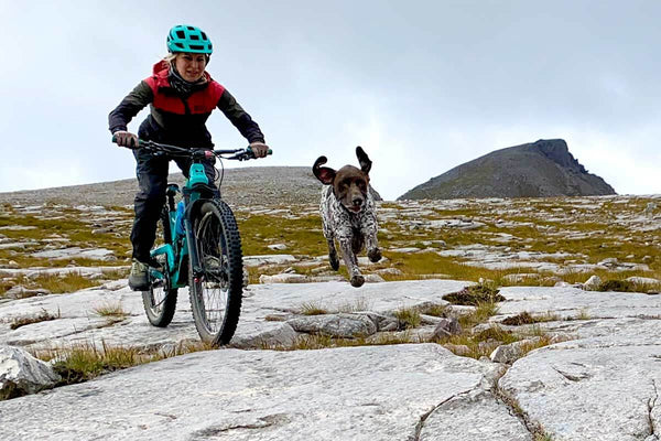 Kate bikes over rocky terrain with a dog running by her side