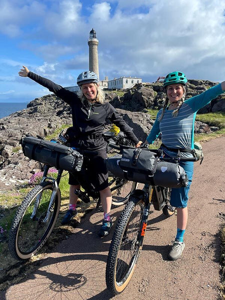 Kate and Shophie stand with their bikes loaded with gear in front of a lighthouse on the coast
