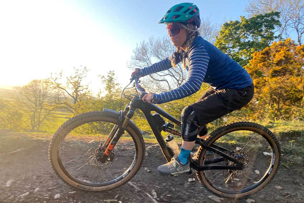 Katee O'Callaghan rides her bike around a curve on a gravel path