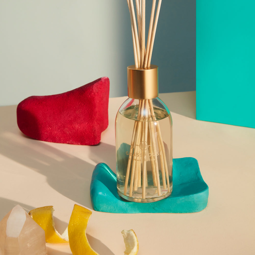scented glasshouse diffuser in a glass bottle with a golden cap