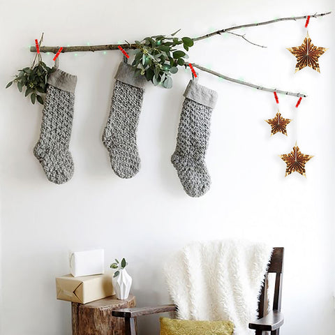 Stockings, plants and stars hung on a branch with Christmas card clip lights