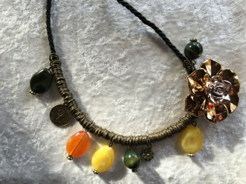 large gold tone rose pendant on long black cord necklace with brass accents