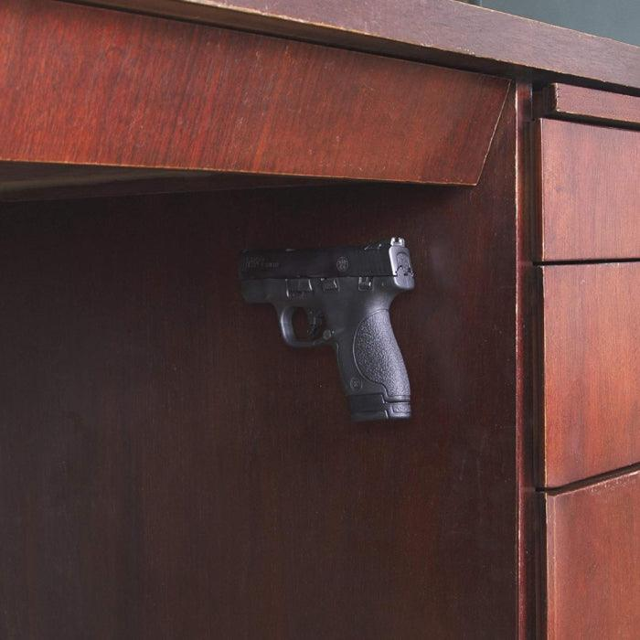 Teknon gun magnet used to mount and hold a handgun on the size of a wood desk.