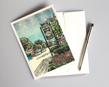 This art card features the Village of Milford, an original mixed media, multi-color linoleum block print by Natalia Wohletz of Peninsula Prints. The design was inspired by the clock on Main Street in Milford, Mich., the linoleum block print depicts the quaintness of many small towns in the United States of America.
