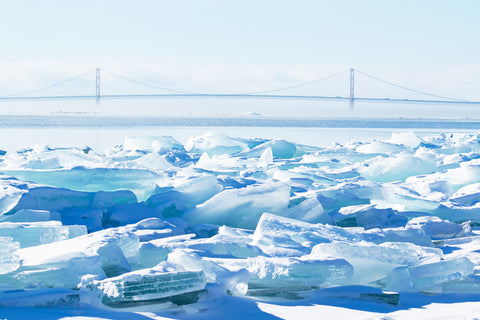 Blue Ice & the Mighty Mac by Jennifer Wohletz.  Photography on canvas. Wind whips mist over the freezing Straits of Mackinac as ice stacks up along the the shoreline. The Mackinac Bridge looks small sitting on the horizon as viewed from Mackinac Island where strong currents stack ice chunks along the shoreline.