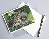 Bird's Nest card features an adorable five-color reduction linoleum block print design of a bird nest housing two eggs hidden among plants in a garden. Created by Natalia Wohletz of Peninsula Prints.