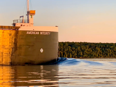 "American Integrity. Photography by Allison Sehoyan. As the freighter American Integrity sails the Great Lakes, the setting sun casts a shadow in the calm water. 8"" x 10"" photograph printed on a digitally stretched metallic canvas. The artist captures images of freighters as they pass Mackinac Island the Mighty Mac."