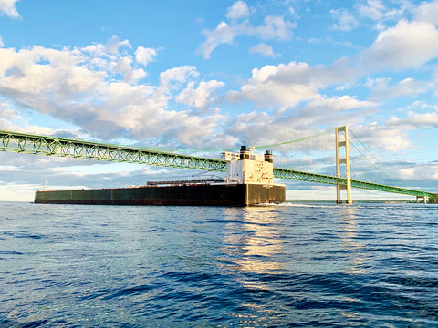 American Century & the Mighty Mac. Photography by Allison Sehoyan.  As the freighter sails beneath the Mackinac Brigde, the setting sun casts its shadow in the calm water.