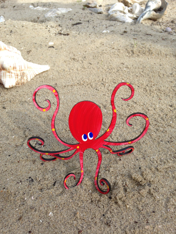 red octopus sculpture on the beach