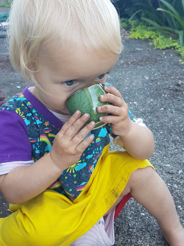 small child drinking from a green tea cup
