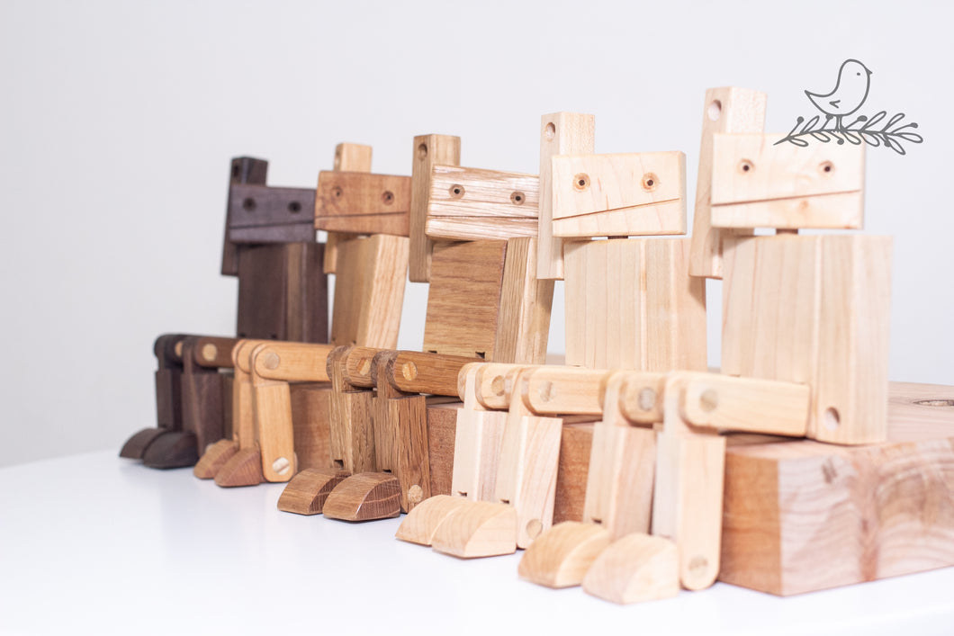 Wooden Robots in varying colours with hands in the air