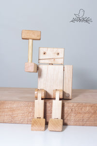 a seated maple wood robot with hammer