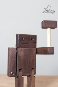 a dark coloured wooden robot with his hammer