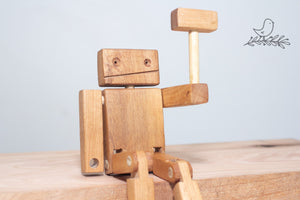 A wooden robot showing off his hammer