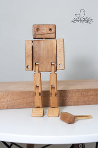 A wooden robot standing with a wooden hammer at his feet