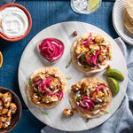 Southwest-Style Cauliflower Tostadas with Cheesy Refried Beans, Pickled Onions, and Lime Crema