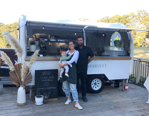 couple and their 1 year old son posing infront of their new food truck with sustainable food - Called the little harvest
