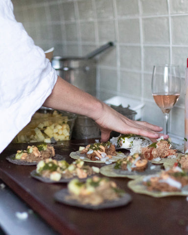 homemade tacos out of a food truck being prepared on a wooden board for customers with a glass of rose in the background