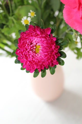 Close up image of a pink Aster flower in a vase with Feverfew daisies.