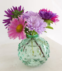 China Aster flowers in a small bud vase. Flowers are pink, mauve and purple.