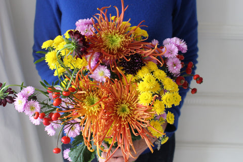 Photograph of a bouquet of flowers being held in front of a blue top. The flowers include yellow, orange and red chrysanthemums, scabious, asters and red berries.