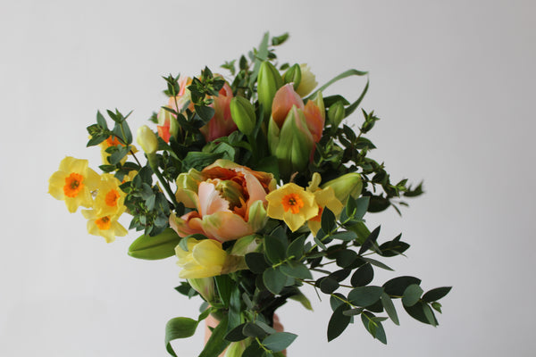 Photograph of a spring letterbox bouquet. The bouquet includes salmon pink tulips, yellow narcissus, lilies and foliage.