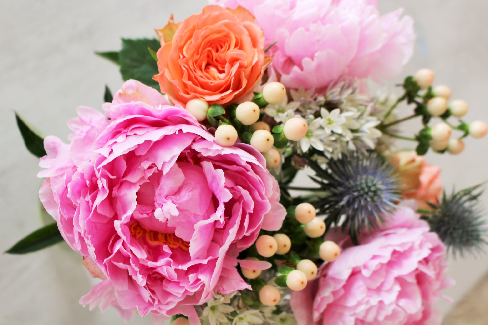 Close up photograph showing a letterbox bouquet of pink peonies, orange roses,  berries, and sea holly.