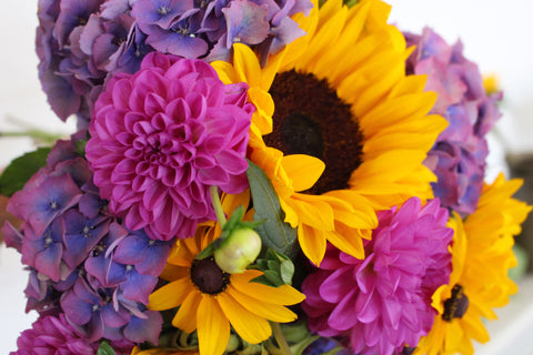 A photograph showing a bouquet of flowers, including a sunflower, rudbeckias, dhalias and hydrangeas. Colours are yellow, purple and blue.