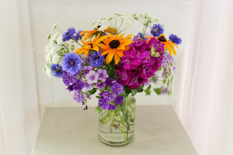 Photograph showing flowers in a glass jar, known as Jam Jar Flowers. They are placed on a table against a white background. The flowers are blue, purple, white and golden yellow and include Stocks, Rudbeckia, Cornflowers and Phlox.
