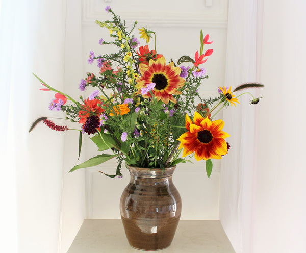 Brown glazed vase holding a mix of brightly coloured flowers, including sunflowers and michelmas daisies.