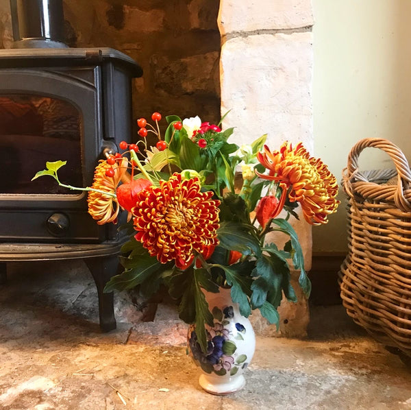 Flowers in a vase next to a wood burner on the left and a wicker basket on the right. The flowers include orange and yellow chrysanthemums, chinese lanterns, alstromeria and sweet williams.