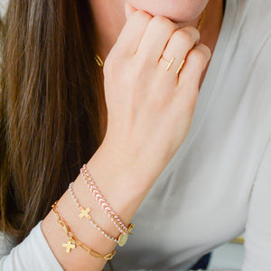 gold vine bracelet with blush pink enamel and disc charm with cross