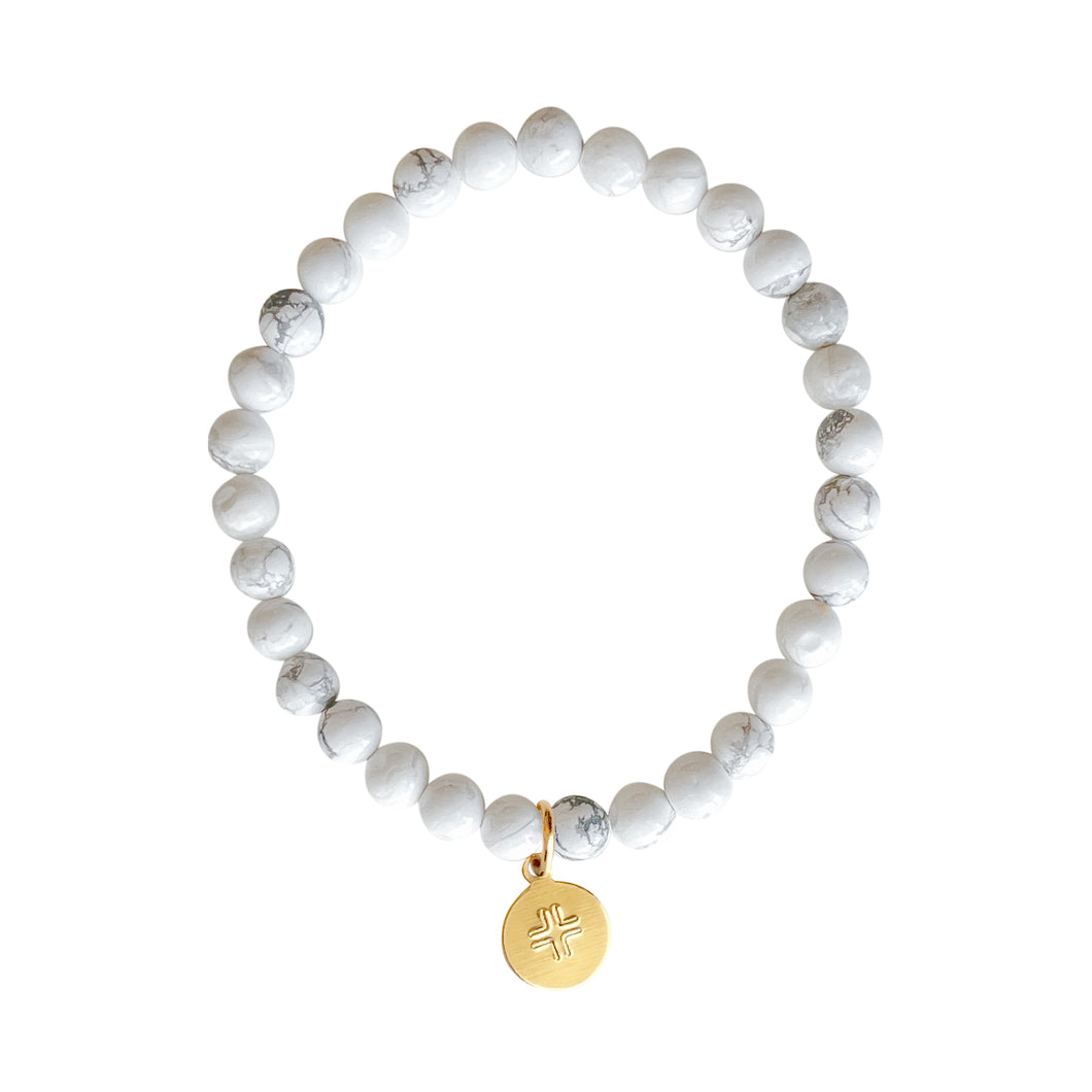 White Howlite stone stretch bracelet with gold disc charm with stamped cross.