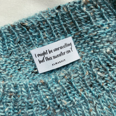 """I might be unravelling but this sweater isn't"" label"