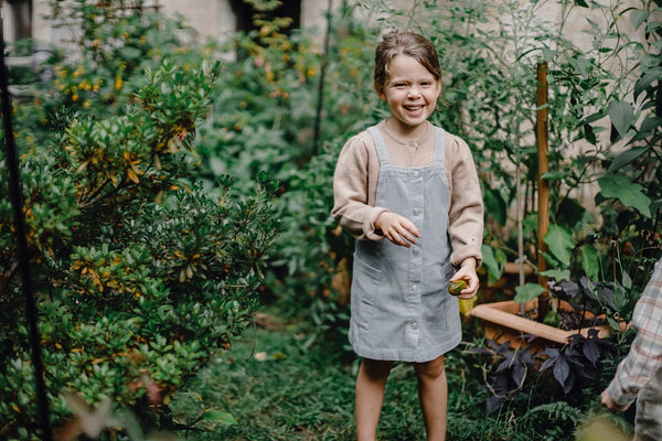 girl smiles while picking fruit from plants