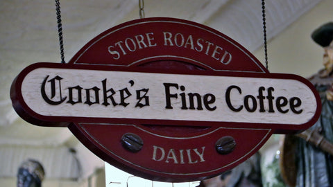 "An old hanging wooden sign in burgundy and white, carved to say ""Cooke's Fine Coffee, Store Roasted Daily""."