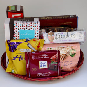 A thin wicker tray holding a selection of products, including: a bag of chocolate wafer cookies, two sleeves of chocolate cookies, 3 assorted chocolate bars, and a box of Rogers chocolates. Exact products vary by order.