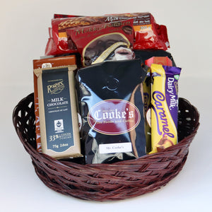 A brown wicker basket holding a selection of products, including: 3 1-pound bags of Cooke's coffee, a sleeve of cookies, 4 assorted chocolate bars, and a bag of chocolate-covered espresso beans. Exact products vary by order.