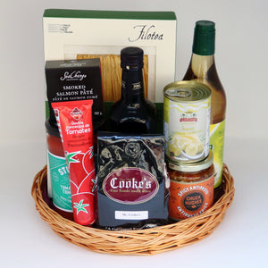 A thin wicker tray holding a selection of products, including: a tube of tomato sauce, a jar of pasta sauce, a jar of antipasto, a can of anchovies, a tin of smoked salmon paté, a box of pasta, a bottle of olive oil, a one-pound bag of Cooke's coffee, and a bottle of dressing. Exact products vary by order.