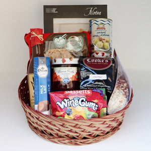 A brown and red wicker basket holding a selection of products, including: a bag of candy, a jar of jam, a one-pound bag of Cooke's coffee, a bottle of dressing, a box of cookies, a bag of risotto, a box of pasta, a can of anchovies, and a container of chocolate. Exact products vary by order.