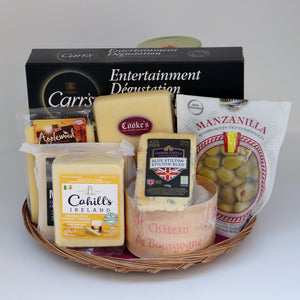 A thin wicker tray holding a selection of products, including: a jar of jelly, a bag of olives, a piece of blue cheese, a wheel of brie, a block of Cooke's cheddar, 3 blocks of assorted cheddar,, and a box of assorted crackers. Exact products vary by order.