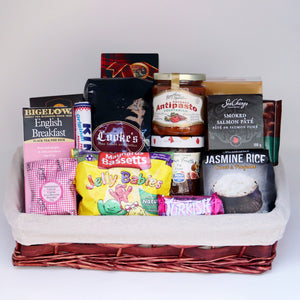 A cloth-lined wicker basket holding a selection of products, including: a box of tea, a tin of salmon paté, a bag of rice, a sleeve of mints, a jar of antipasto, a box of cookies, a jar of jam, 3 chocolate bars, a 1-pound bag of Cooke's coffee, a bag of candy, and a box of spices. Exact products vary by order..